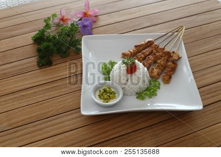 Satay Or Sate Ayam With Rice And Vegetable, Wood Background.