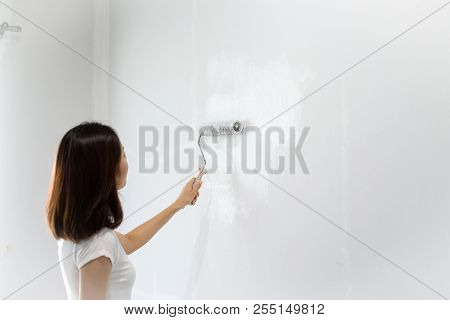 Young Asian Woman Painting On A White Wall