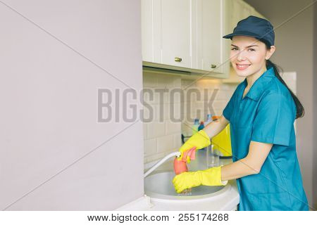 Positive And Nice Cleaner Stands At Sink And Looks On Camera. She Washes Water Tube. Girl Is Cleanin