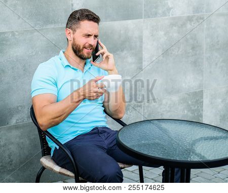 Coffee break brings physical and mental wellbeing. Time to relax. Brief coffee break provides employees with quick ways to relax. Man sit terrace and drink cappuccino speak phone grey wall background. poster