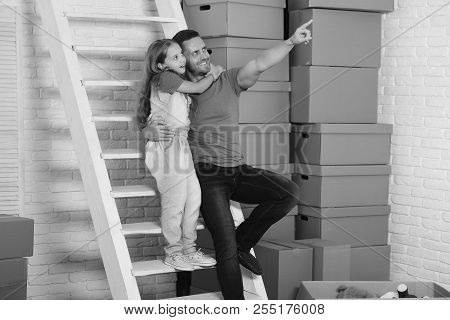 Daughter And Father Sit On White Ladder Near Pile Of Boxes. Girl And Man With Smiling And Surprised