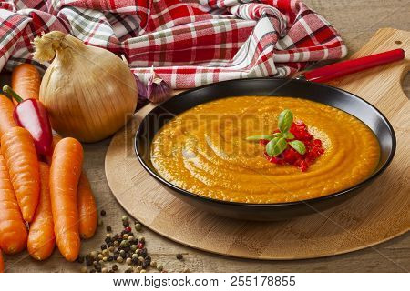 Roast Carrot Soup - Thick Roast Carrot Soup With Its Ingredients, Carrots, Onion. Chilli And Garlic.