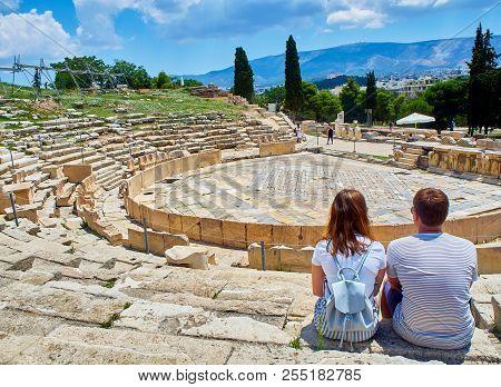 A Couple Of Tourists Admiring The Theatre Of Dionysus Eleuthereus. Acropolis Of Athens. Attica Regio