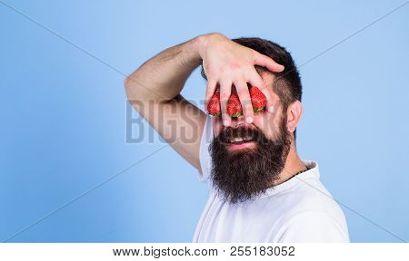 Dream of strawberry. Man bearded hipster hold hand with strawberries in front of eyes. Glance of man blocked by berries. Strawberry on my mind. Man can not see anything but strawberry blue background. poster