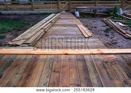 A Wooden Walkway After The Rain On The Construction Of A Frame House