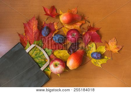 Colorful Autumn Maple Leaves  And Fruits In Brown Paper Bag. Sale And Shopping Concept.