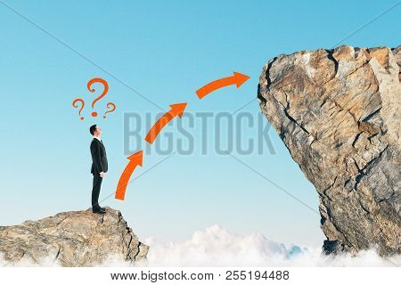 Side View Of Young Businessman On Small Cliff Thinking How To Get Onto Big One. Career Development A