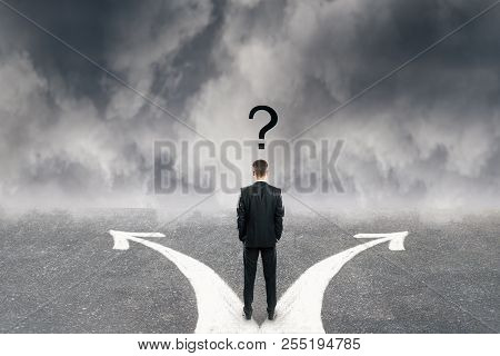 Back View Of Young Businessman With Question Mark And Two Arrows On Concrete Road. Cloudy Sky Backgr