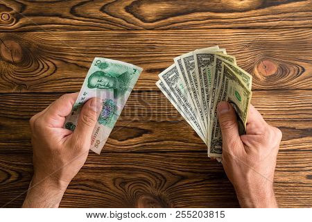 Man Holding Chinese Yuan And A Fanned Fistful Of United States Dollars In His Hands Over A Wooden Ta