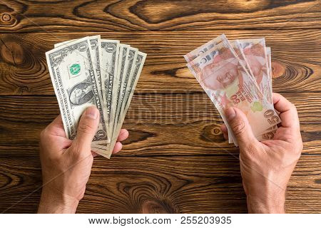 Man Holding Usd And Turkish Lira In His Hands Over A Wooden Table Viewed From Above In A Concept Of