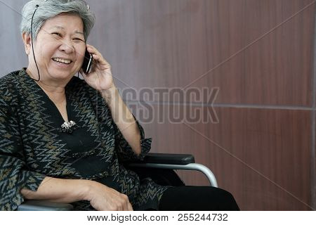 Elder Woman In Wheelchair Talk On Mobile Phone. Elderly Female Speaking On Smartphone. Senior Have P