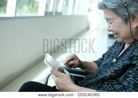 Elder Senior Woman In Wheelchair Holding Tablet. Elderly Female Texting Message, Using App With Touc