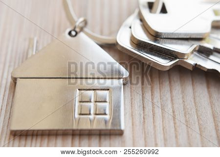 Three Keys In Key Chain With House Shaped Pendant On Natural Wood Background Closeup View With Copy