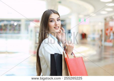 Happy Woman Holding Shopping Bags And Smiling At The Mall.