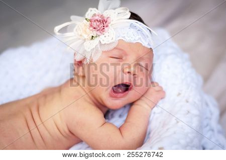 Cute Tiny Newborn Caucasian Girl Yawning Closeup Portrait. Kid Bow Elastic Band On Her Head. A Two W