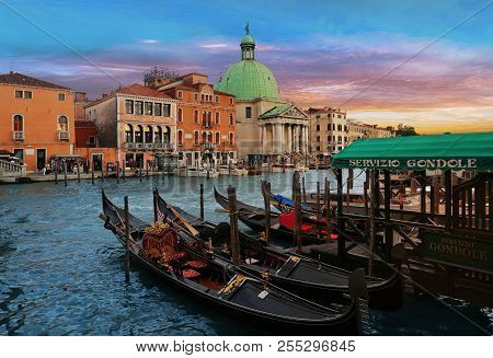 Venice, Italy, Jun 8, 2018: Moored Gondolas In Foreground With San Simeon Piccolo Church In The Back