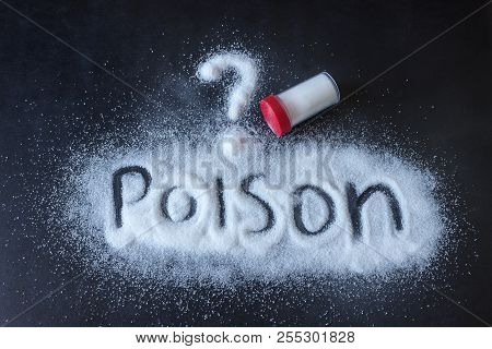 Salt scattered on black surface. Written word- poison. Concept- healthy food, diet, harm to health from excessive consumption of salt and sugar. poster