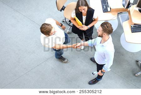 Top View Of Young Business Partners Shaking Hands Over Deal At Office. Focus On Hand Shake.