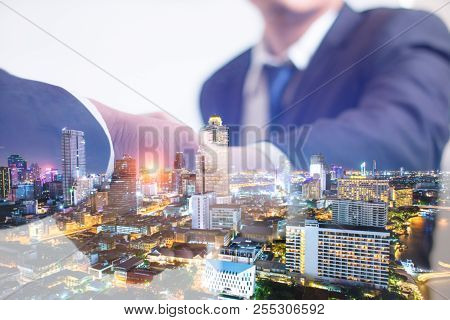 Double Exposure Concept. Investor Business Handshake With City Night Background. Businessman Shaking