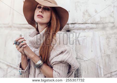 Boho jewelry on model: ethnic rings, bracelets and earrings. Beautiful woman wearing warm woolen sweater, hat and fashion jewellery. Street photo in pastel tone.