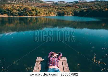Young woman resting on peer and enjoying lake view in autumn. Good sunny day for resting outdoors and travel.