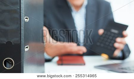 Male Arm In Suit Hold Calculator Showing Calculator In Office Closeup. Outraged Boss Shows On The Ca