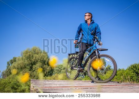 Young bicyclist rides on mountain bike on the bridge poster