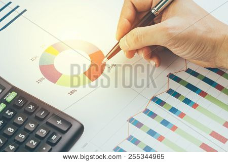 Female Hand Holding Pen Reviewing Pie Chart And Graph Information Report With Calculator On Office D