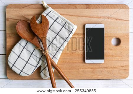 Kitchen Utensils On Wooden Background With Smart Phone And Copy Space