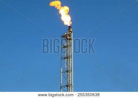 Gas Flare Is Releasing And Burning To The Atmosphere At An Offshore Gas Platform With Sky.