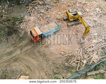 Demolition Site Top View. Industrial Excavator Unloading Debris And Rubble In Truck.