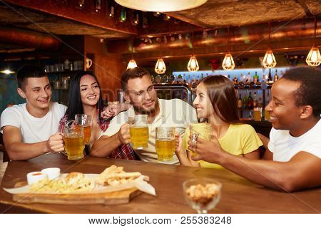 Company Of Happy Friends Sitting In Bar At Table With Beer And Snacks, Drinking Beer. All People Rai