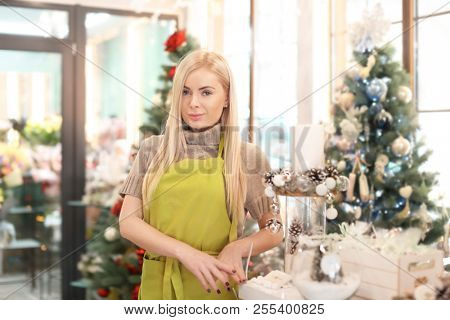 Young woman standing in flower store. Small business owner