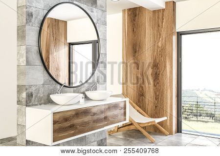 White Double Sink On Wood Counter With A Round Mirror Hanging Above It In A Luxury Marble And Wooden