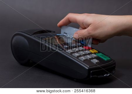 Hand Swiping Credit Card In Store. Female Hands With Credit Card And Bank Terminal. Color Image Of A