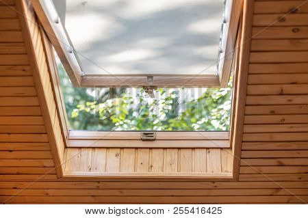 Opened Roof Window With Blinds Or Curtain In Wooden House Attic. Room With Slanted Ceiling Made Of N