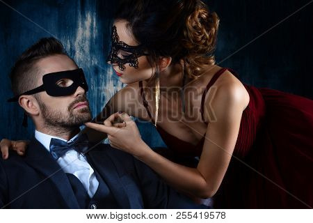 Sexy woman female in black carnaval mask red expensive dress and gold earnings seduces millionaire man male in suit, bow tie and black carnaval mask. Sex, tempts, harassment, sexism, seduction issues poster