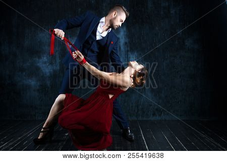 Couple In Dating. Rich Man Male Dress Skirt Tying Woman Hands. Woman Female In Expensive Red Evening