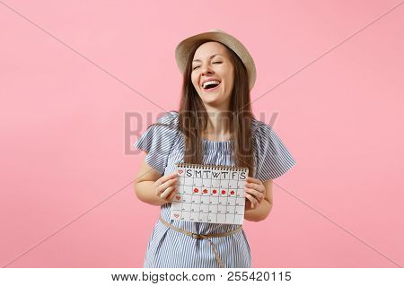 Portrait Of Excited Woman In Blue Dress, Hat Holding Periods Calendar For Checking Menstruation Days