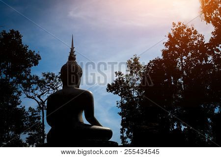 Silhouette Of Buddha With Blue Sky Background