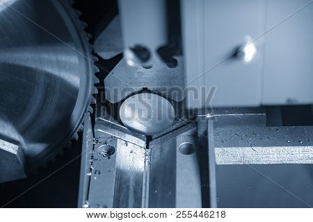 The  Band Saw Machine Cutting Raw Metals Rods In The Light Blue Scene.the Industrial Sawing Machine