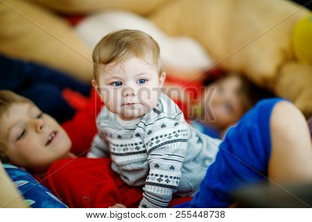 Little Kid Boy Hugging With Newborn Baby Girl, Cute Sister. Siblings. Brother On Background. Kids Bo