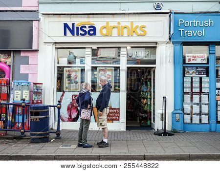 Portrush / Northern Ireland 13/07/15 - Two People Chatting Outside A Newsagents In Portrush