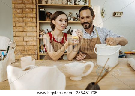 Couple Of Ceramists Sitting At The Table Making Their Handiworks