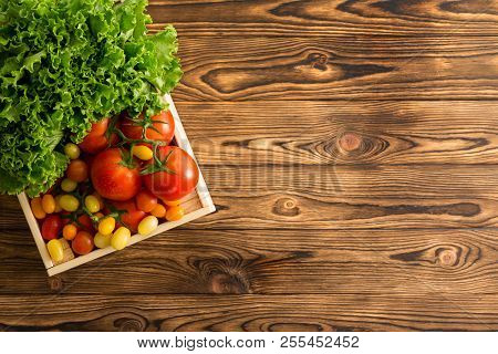 Assortment Of Ripe Whole Tomatoes And Head Of Fresh Green Lettuce In A Small Wooden Box On A Table W