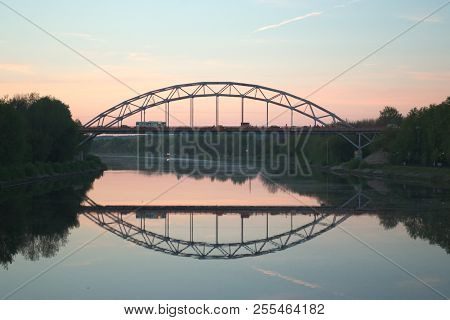 Bridge Over The River At The Evening Dawn. View From The River To The Bridge At The Sunset