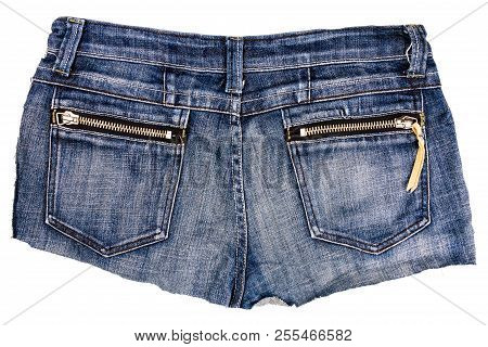 Piece Of Blue Jeans Fabric With A Back Pockets Isolated On White Background. Rough Uneven Edges. Den