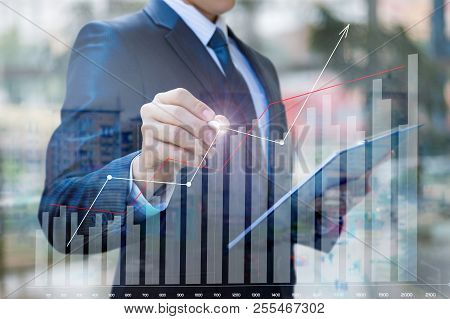 Businessman Draws A Graph Of Financial Statistics On A Blurred Background.