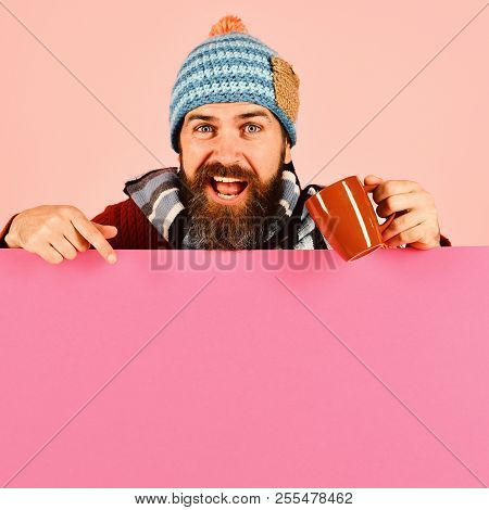Hipster With Beard And Excited Face Has Warm Tea Or Coffee Pointing Down. Autumn And Hot Drinks Conc