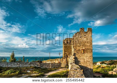 Genoese Fortress In Feodosia, Crimea, Russia. Beautiful Panorama Of Ancient Ruins At Sunset In Crime
